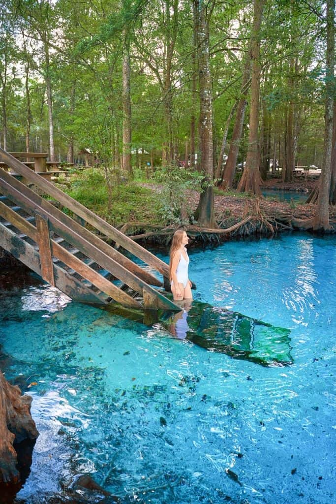 walking down stairs into crystal clear blue water at Ginnie Springs in Florida