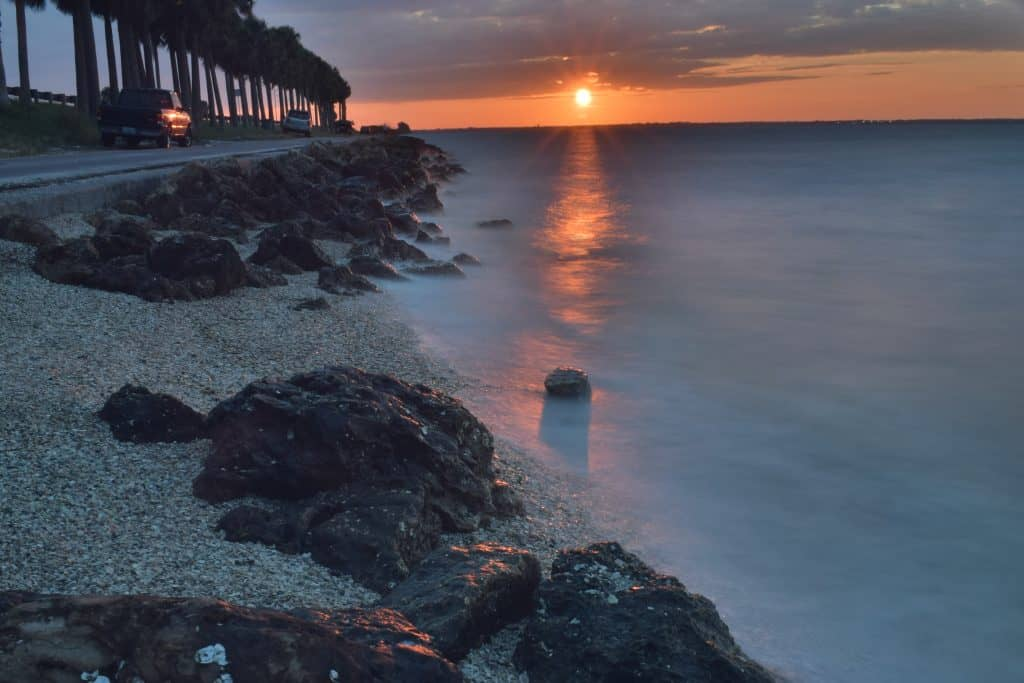 The waves lap at the rocky beach and trail along the Courtney Campbell Causeway Beach at sunset.