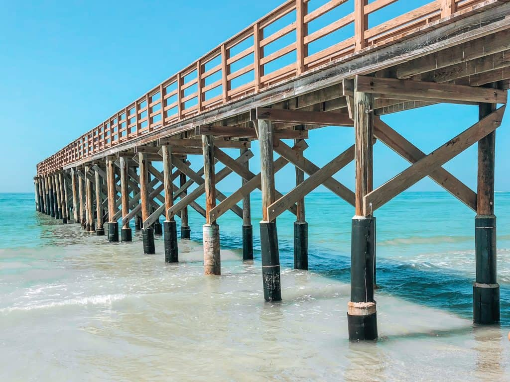 The waters lap at the pier on the shores of Redington Beach, one of the best beaches in Clearwater!
