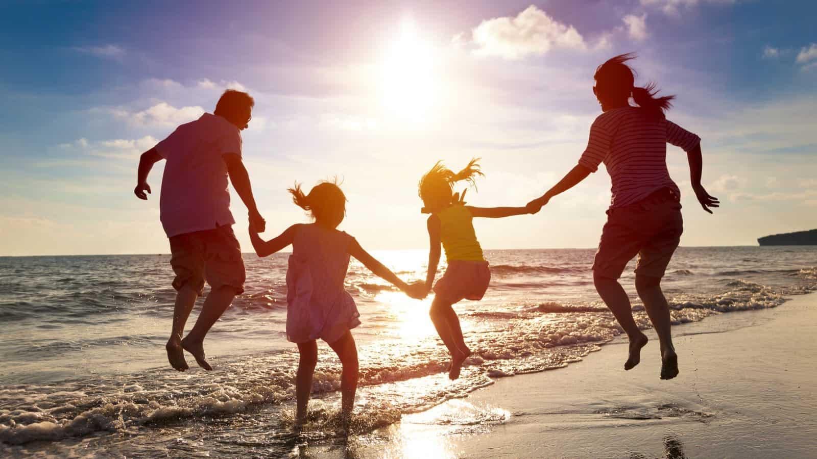 A family jumps as the waves crash on the beach.