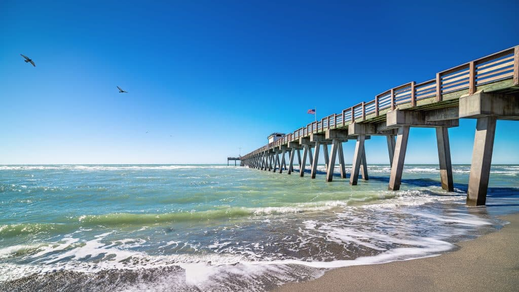 The emerald waters of the Gulf lap at the shorelines underneath the pier at Venice Beach, Florida.