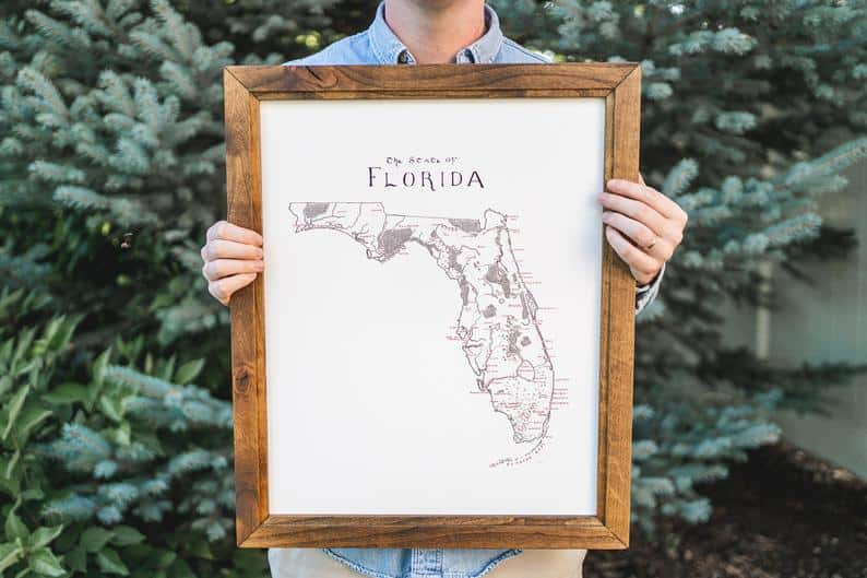 Photo of a man holding a map of Florida, one of the best Florida gifts and souvenirs.