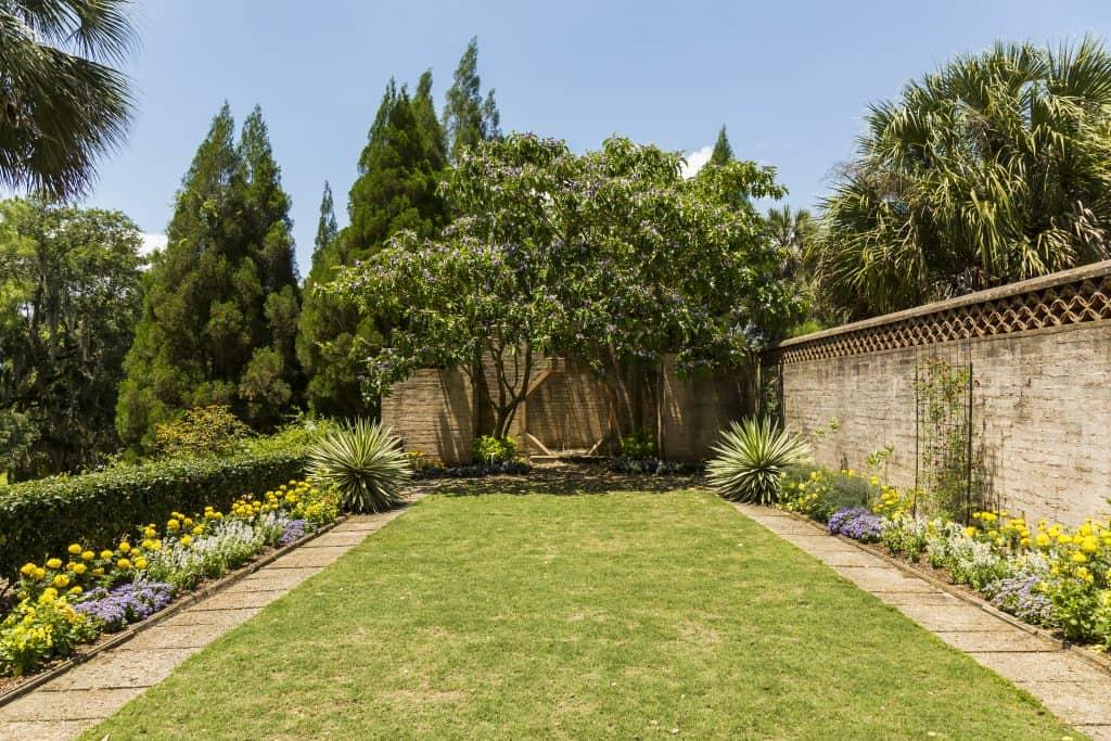 An octagonal door lies at the edge of a garden along the trails at Bok Tower Gardens.