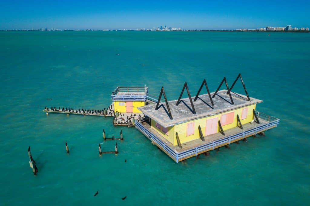 A colorful home hovering over the green waters in Stitlsville is covered in birds in Biscayne Bay, one of the best things to do in Miami.
