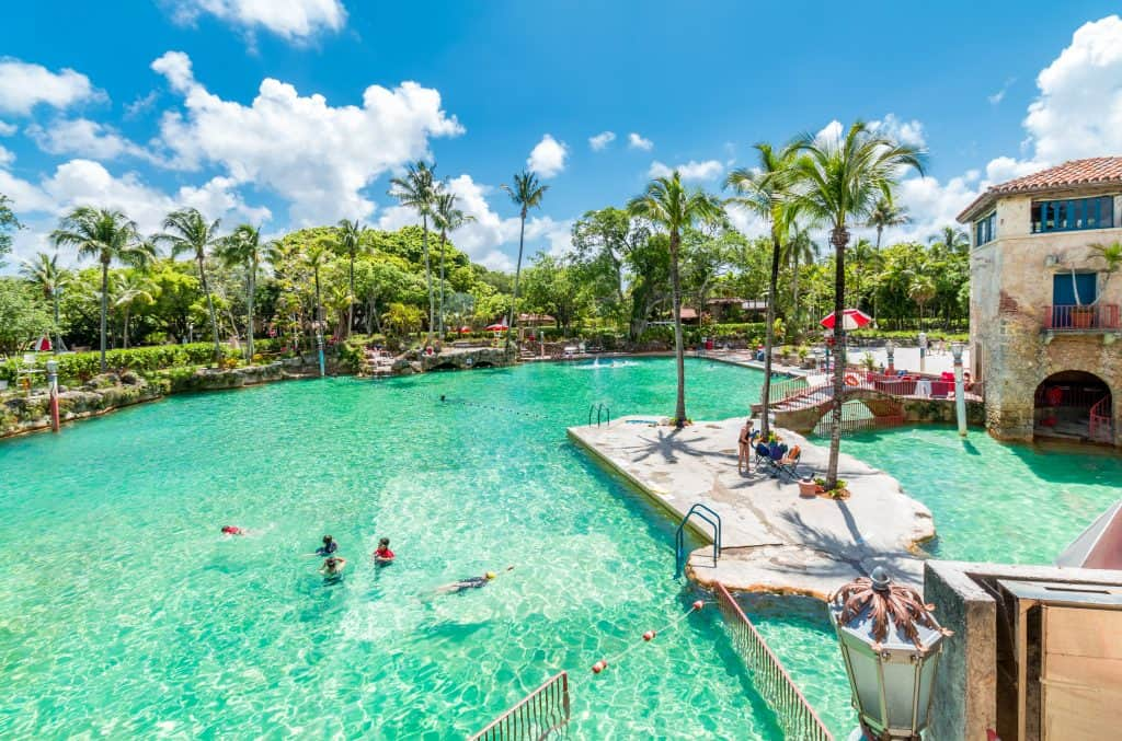 The Venetian Pool glitters and sparkles in the sunlight as swimmers enjoy its clear waters in Miami Florida.