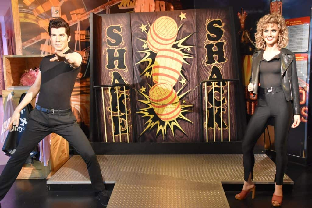 Realistic wax sculptures of Sandy and Danny from Grease stand in Madame Tussauds in Orlando.