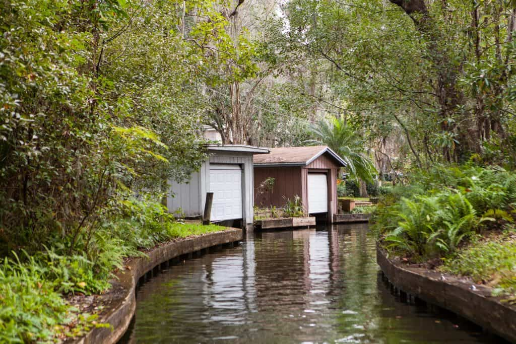 The view of boat sheds along a canal connecting the seven lakes of Winter Park, as seen from the Winter Park Scenic Boat Tour, one of the best things to do in Orlando.