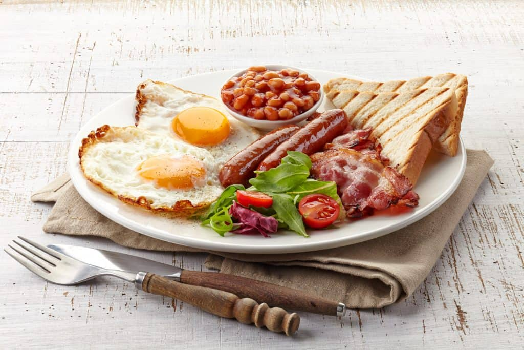A breakfast of two eggs, beans, toast, sausage, and bacon sit on a plate, ready to be eaten.