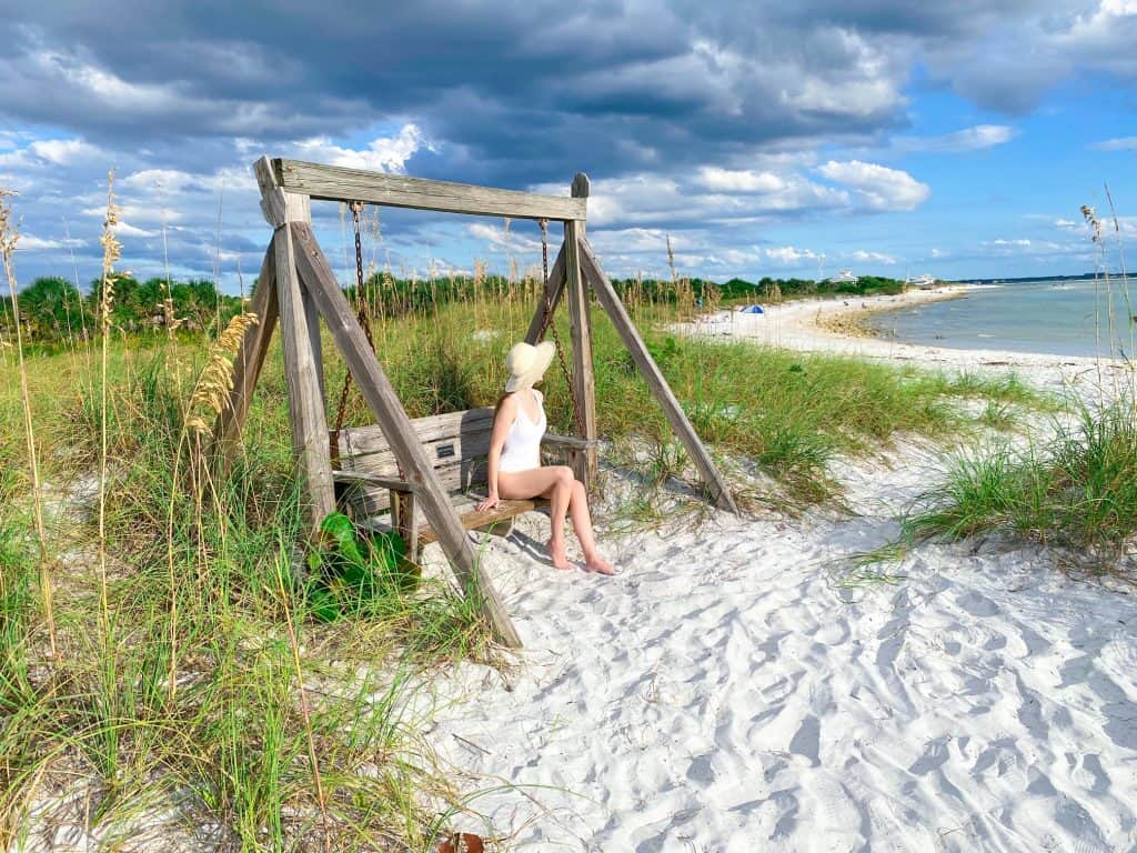 swinging on a wooden swing at honeymoon Island state park