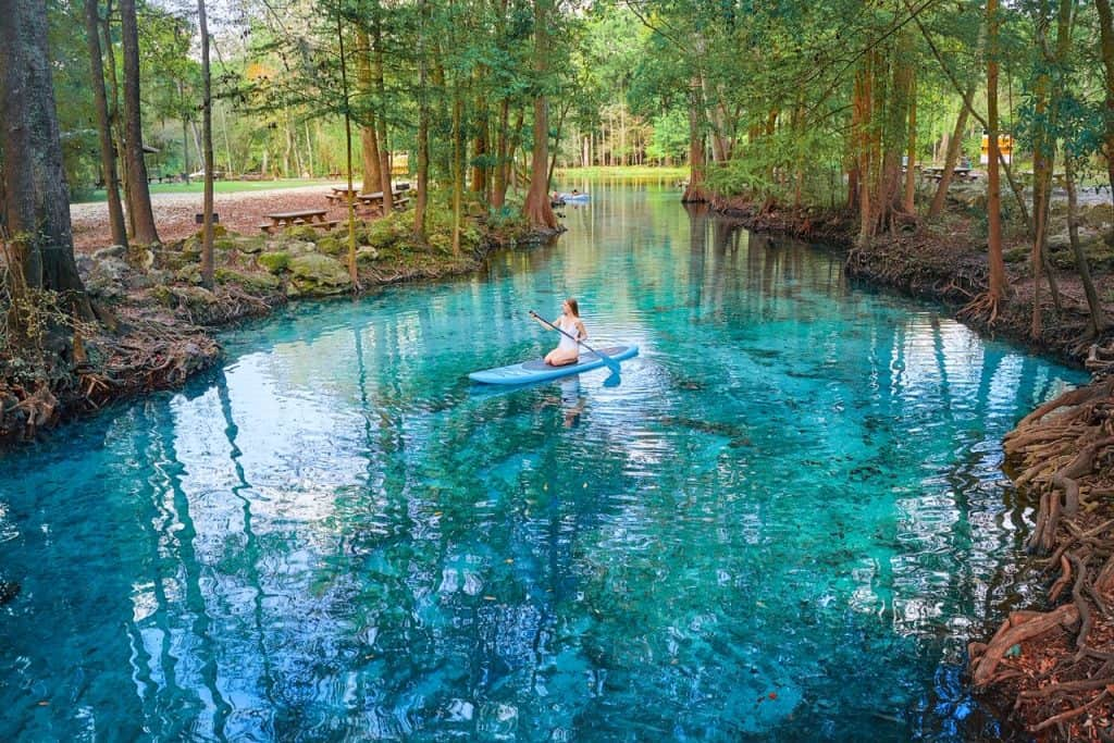 Paddle boarding along the clear blue waters of Ginnie Springs, one of the best destinations for kayaking in Florida.