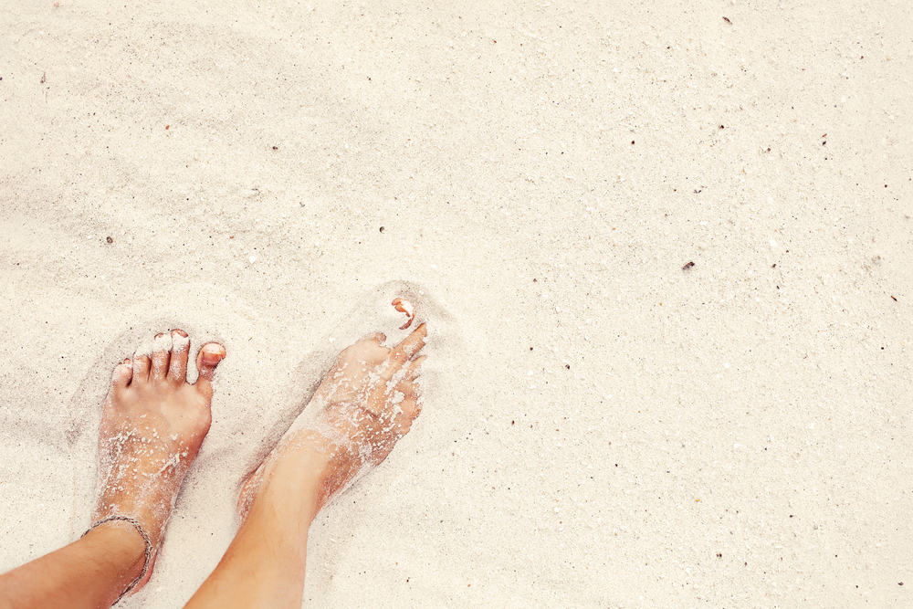 Girls feet in the sand in an article about Key West Beaches