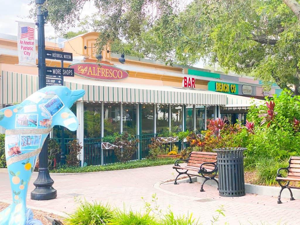 A brick walkway, benches, and a Florida dolphin sit outside the garden patio of Cafe Alfresco.