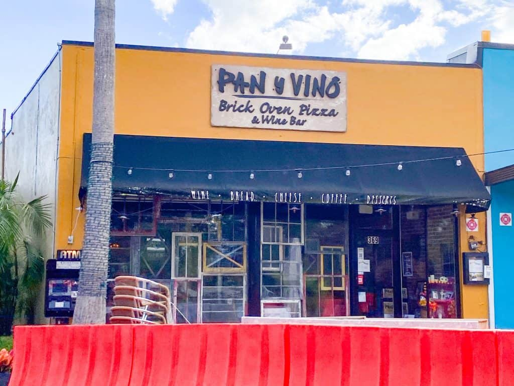 The mustard yellow exterior of Pan Y Vino, a combination pizzeria and wine bar.
