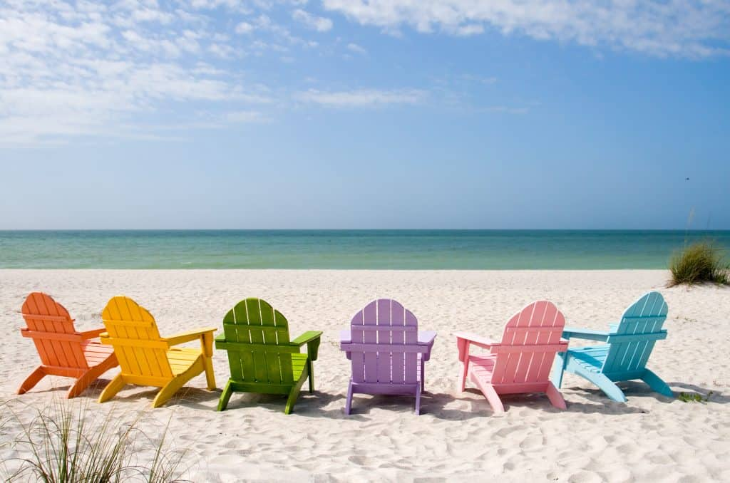 Colorful chairs are arranged on the sand to face the shoreline of Captiva Beach.