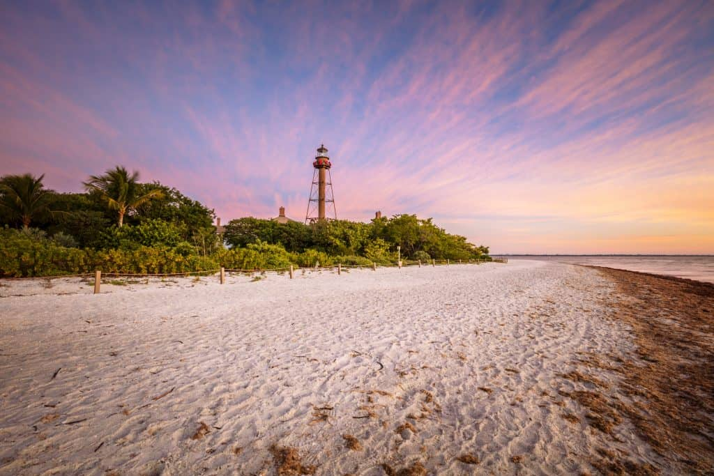 The sun sets, making the stretched clouds appear pink, over the Sanibel Lighthouse Beach, one of the best Sanibel Island beaches.