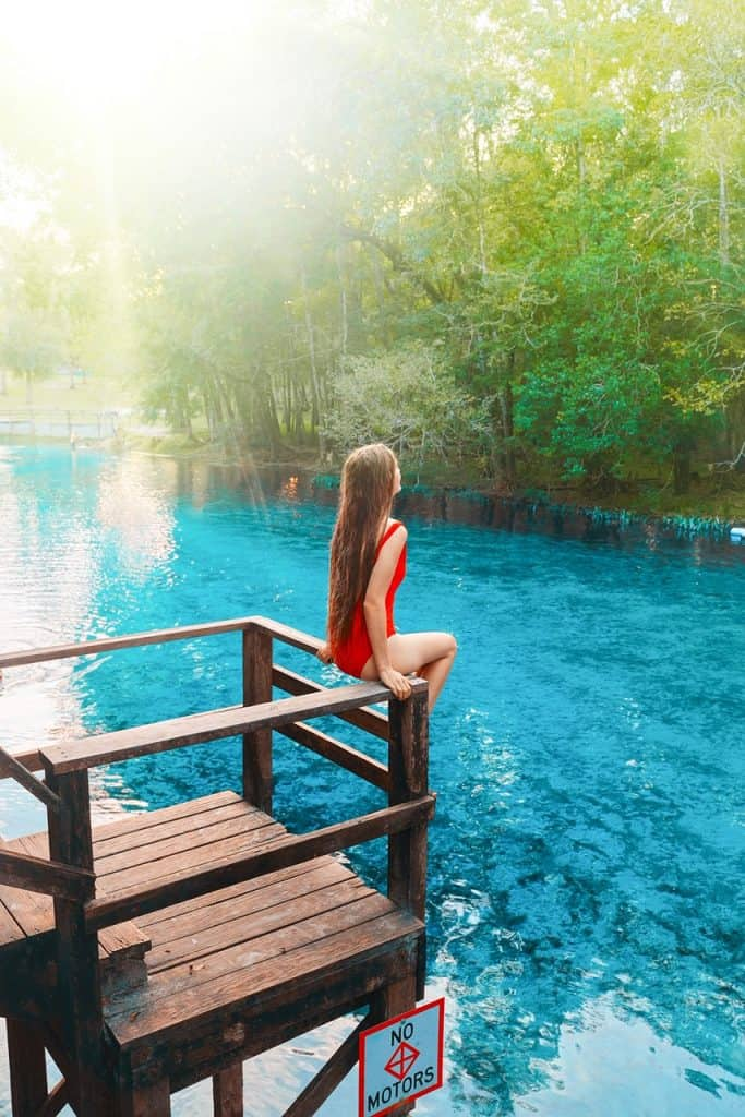 A girl sat on the railings at Gilchirst Blue Spring