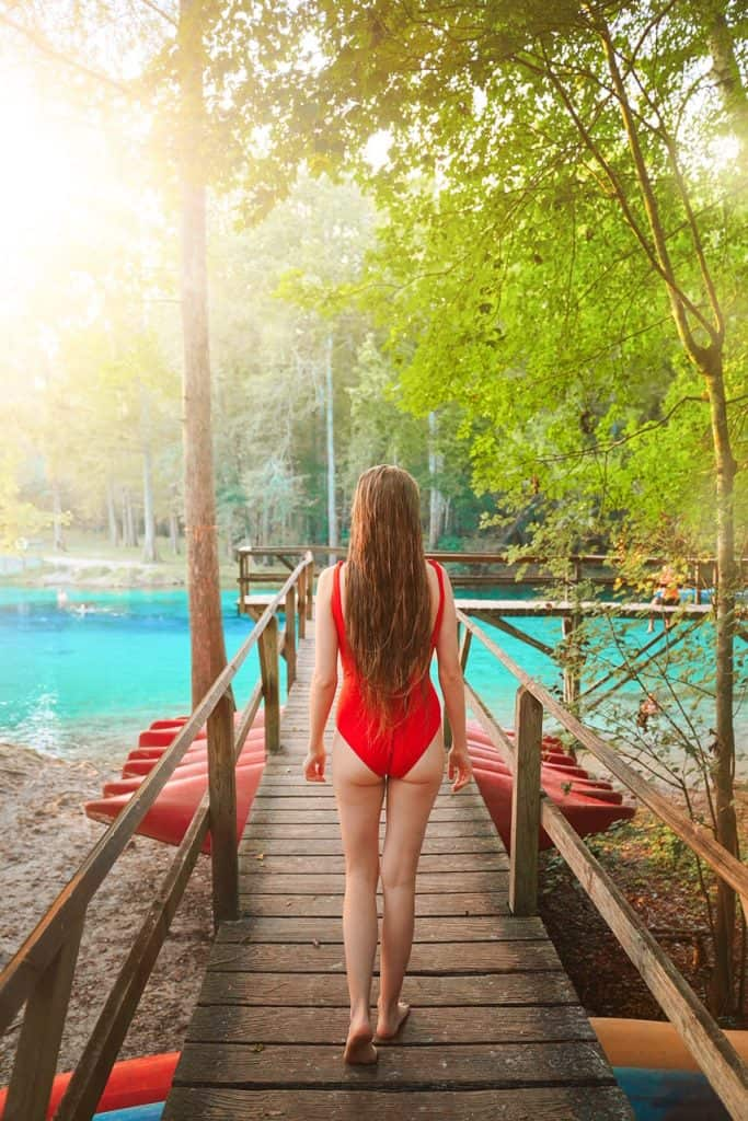 A girl walking on a broadwalk to a spring in an article about springs near Jacksonville