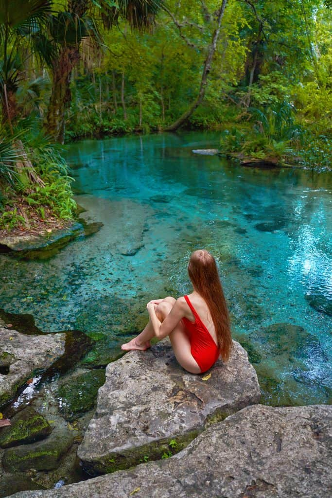Girl sat on a rock looking out at the blue water of Rock Springs