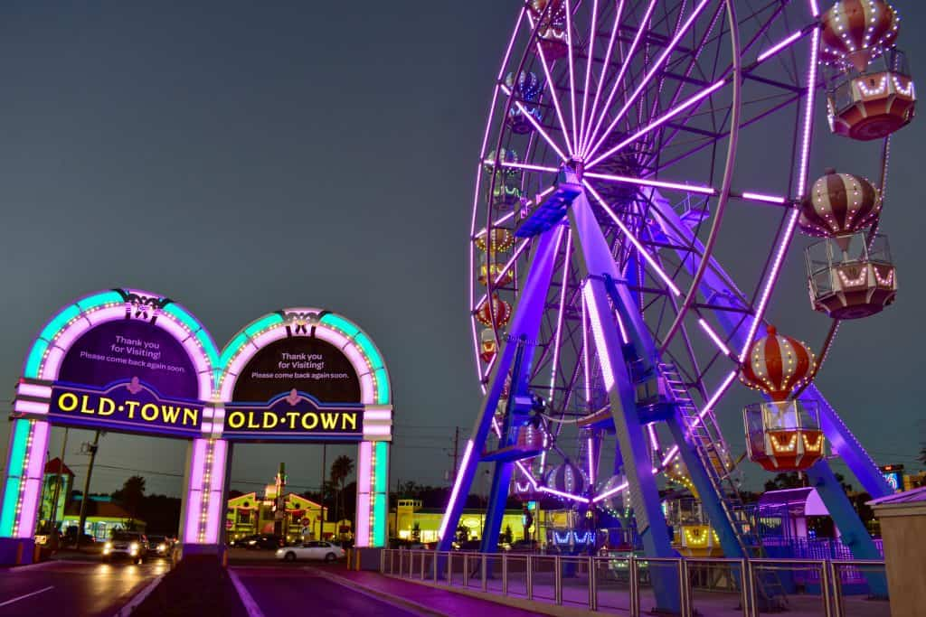 The entrance to Old Town is lined with pastel neon lights, right next to the iconic Ferris Wheel.