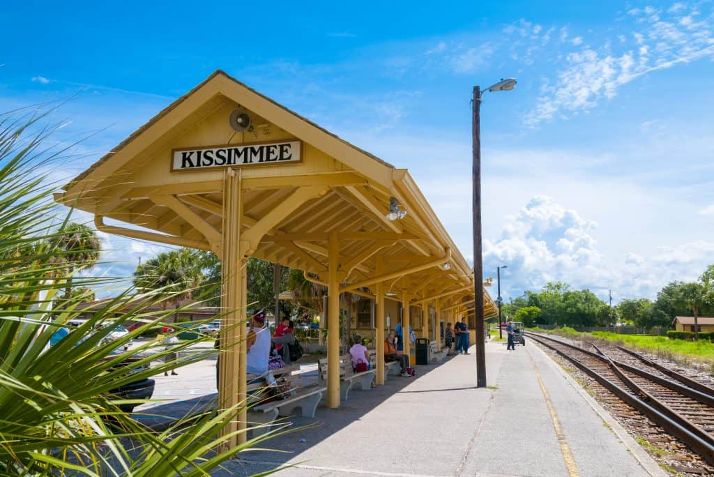 A train depot sits in the city, marked with the town's name, as guests wait.