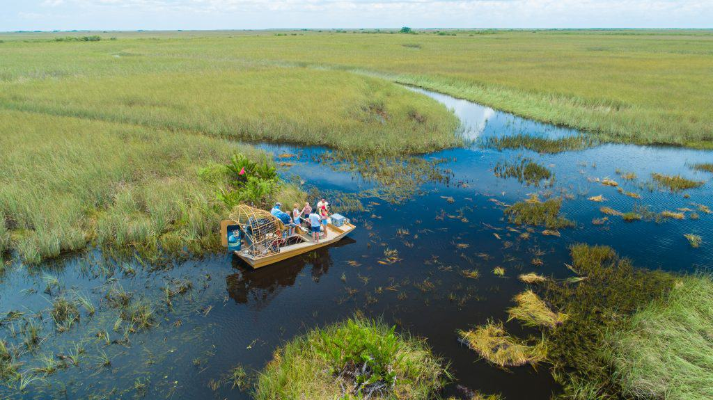 A pontoon floats on the murky waters of the Everglades, one of the best things to do in Marco Island.