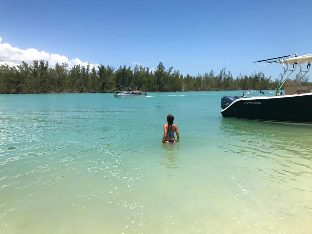 A swimmer wades from the boat to sink into the warm, blue waters of Keewaydin Island, one of the best Marco Island activities.