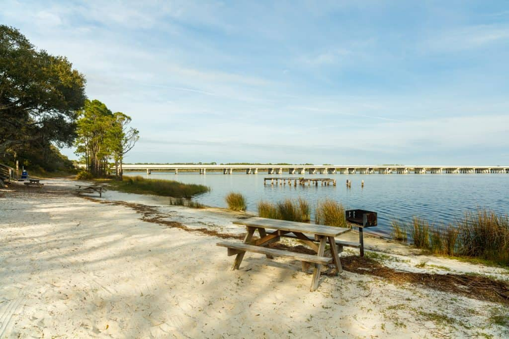 A picnic table and grill sit on the coastal dunes of Camp Helen State Park, one of the best things to do in Panama City Florida.