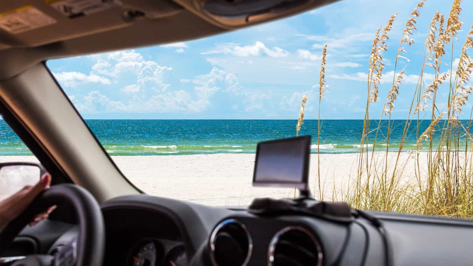 A GPS sits on the dashboard of a car overlooking the beach, ready for a Florida road trip.
