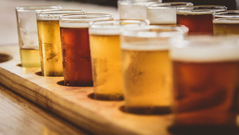A beer flight sits on a bar, each selection a slightly different shade of amber.