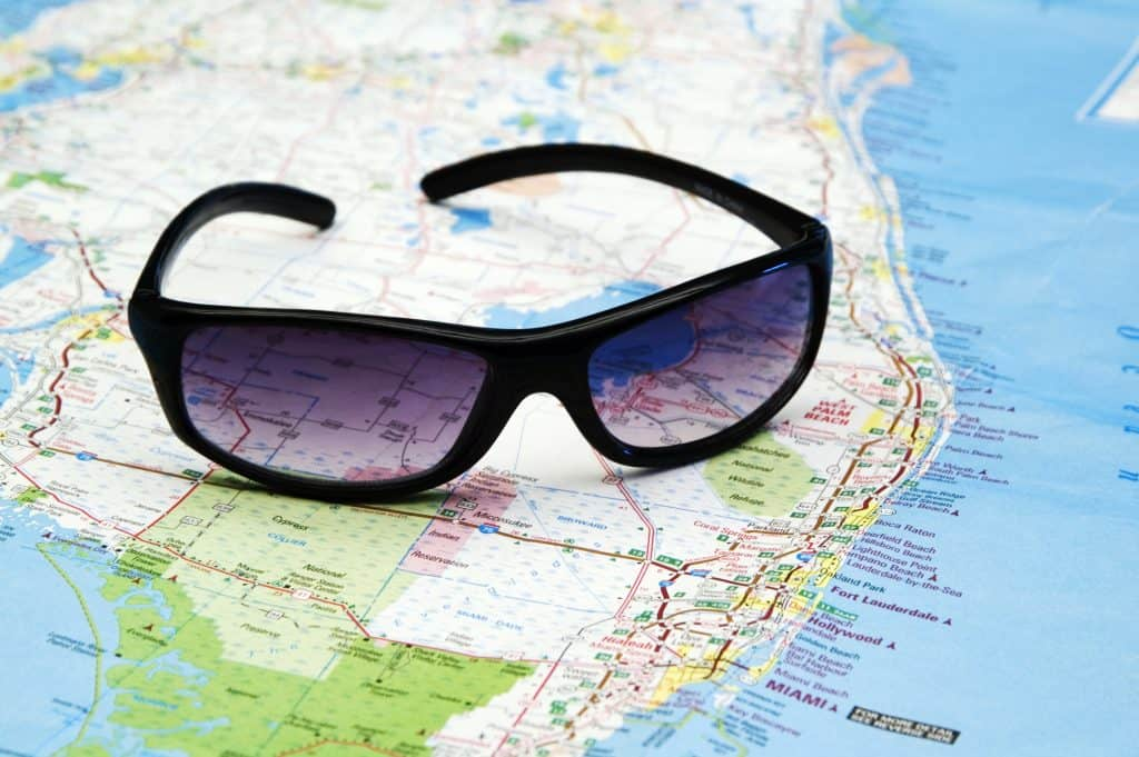 A pair of sunglasses sits on top of a map of Florida, ready for you to hit the open road.