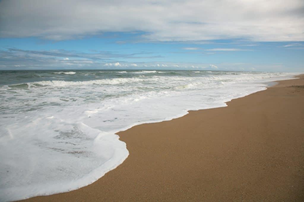 The dark brown sands of Apollo Beach lie under beautiful waves.