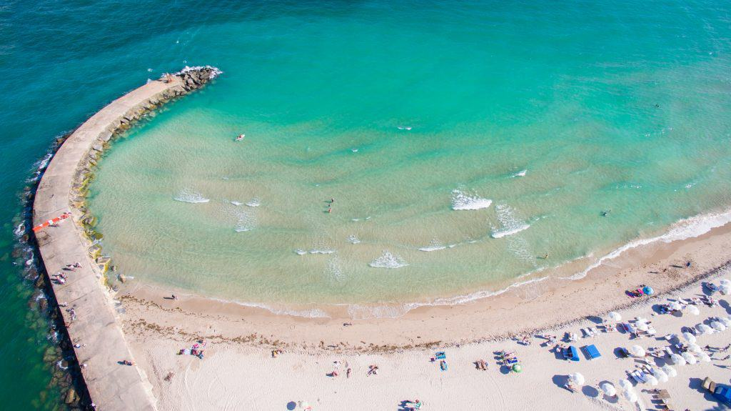 An aerial view of the clear blue waters of Haulover Beach, one of the best nude beaches in Florida.