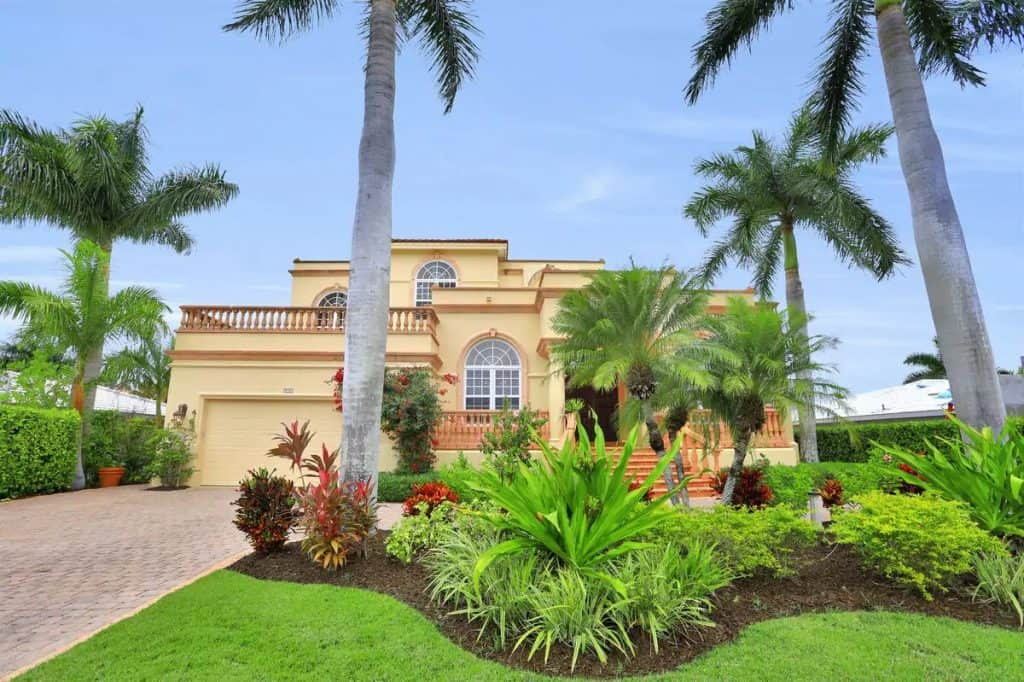 Photo of the exterior of a grand two story waterfront home in Florida.