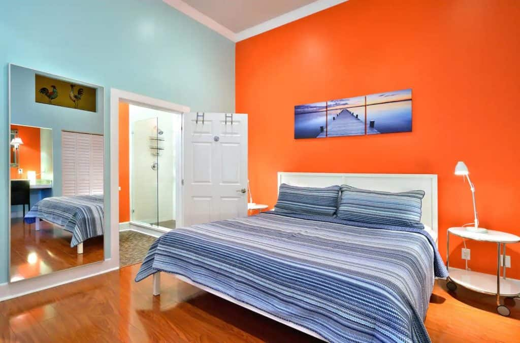 Photo of a bedroom with a bright orange accent wall at an Airbnb in Florida.