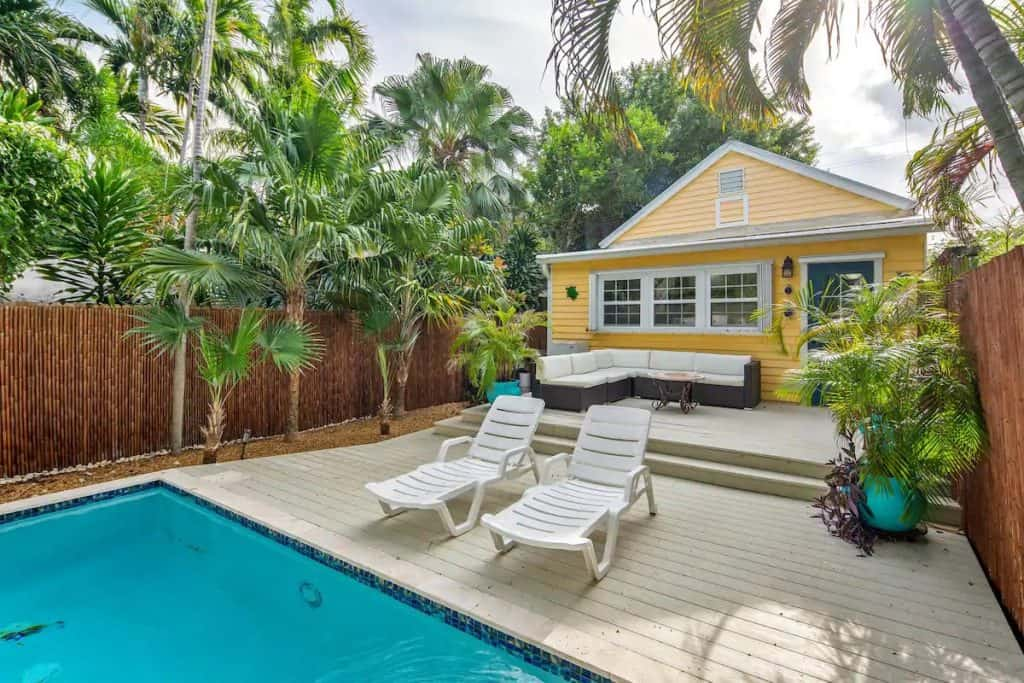 Photo of a yellow home with a back pool deck and seating area.
