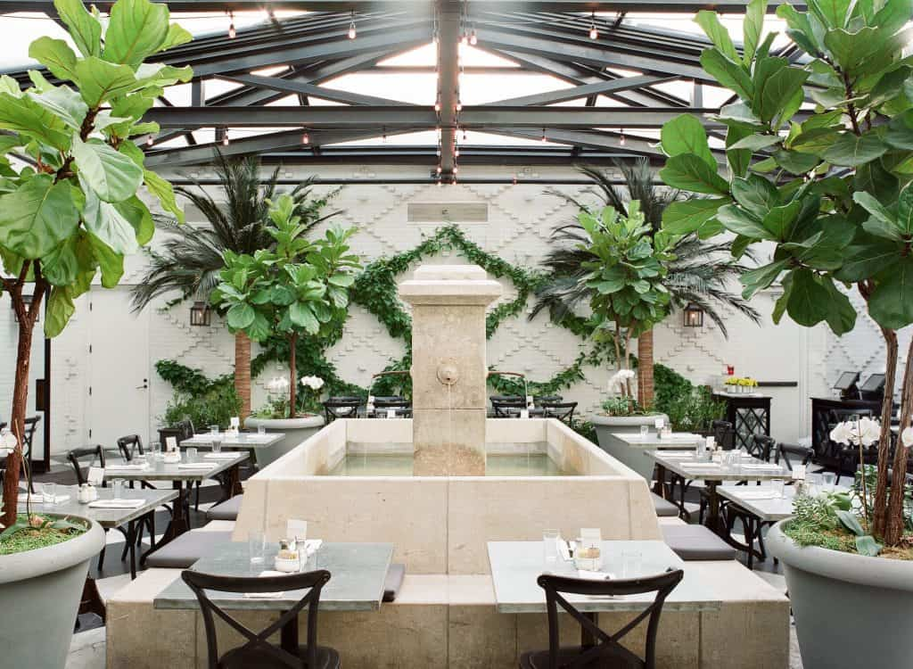 The garden dining area of Oxford Exchange, one of the best downtown Tampa restaurants, complete with its fountain in the center.