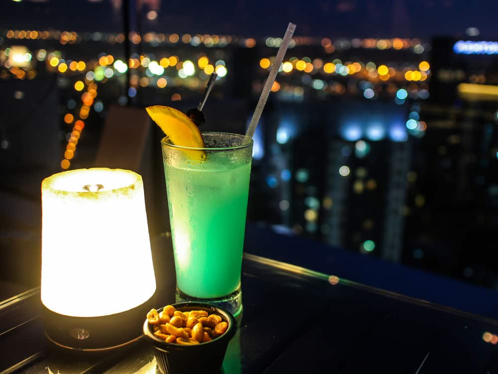 Two drinks with the night sky in the background in an article about rooftop bars in Orlando