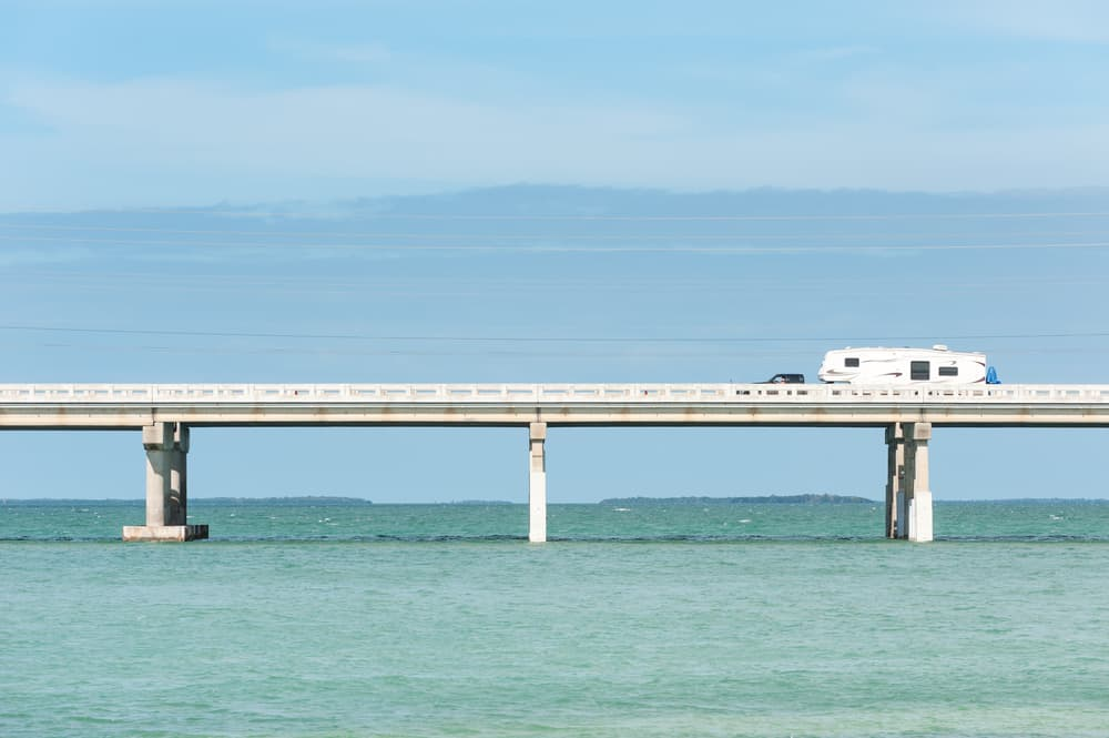 The Florida Keys bridge with a car driving on it.