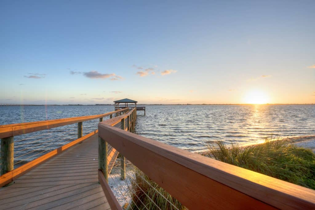 The sun sets on the waters near Melbourne Beach as seen from a dock jutting out into the ocean.