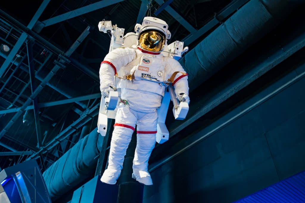 A space suit hangs over the crowds as they pass through the exhibits of the Kennedy Space Center.