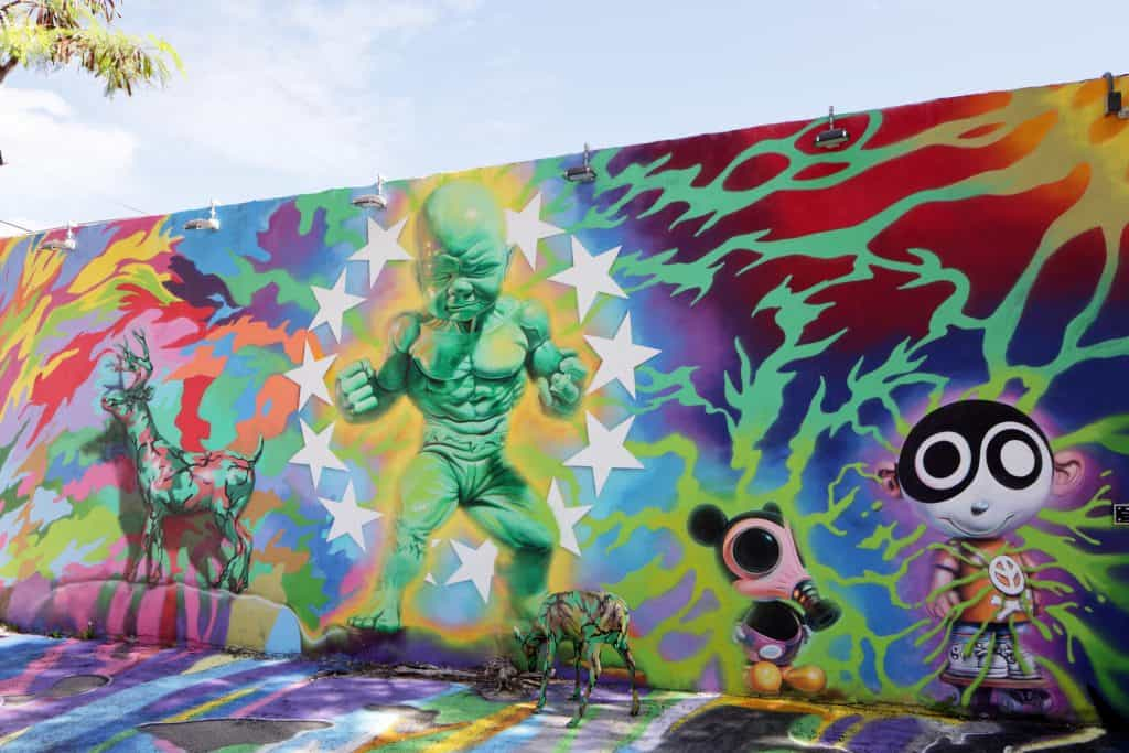 A mural features a green baby with muscles and Mickey Mouse wearing a gas mask.