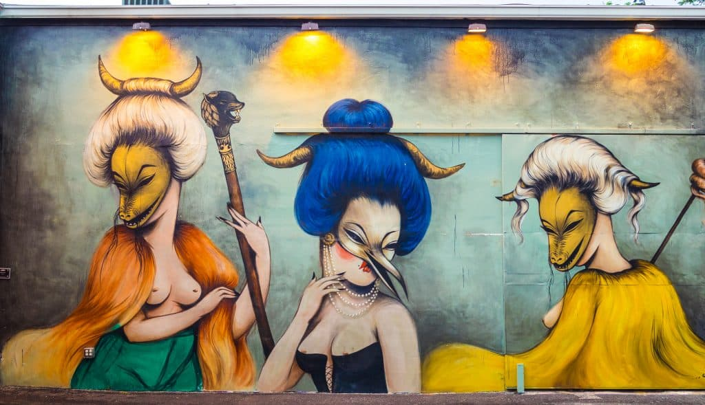 A mural at the Wynwood Walls depicts three women wearing masks representing various animals.