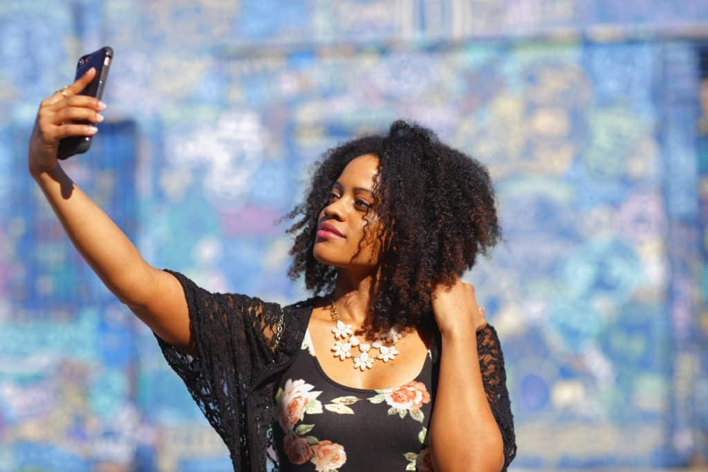 A woman poses for a selfie in front of the Wynwood Walls.