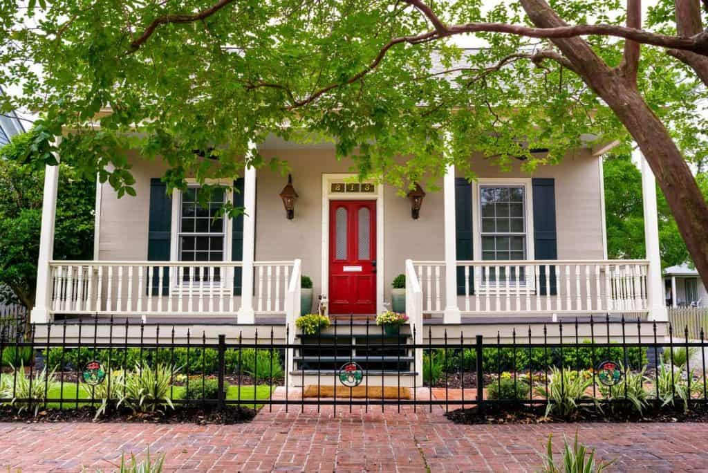 Photo of the exterior of an 1850s Historic Cottage Airbnb in Florida with a bright red door.