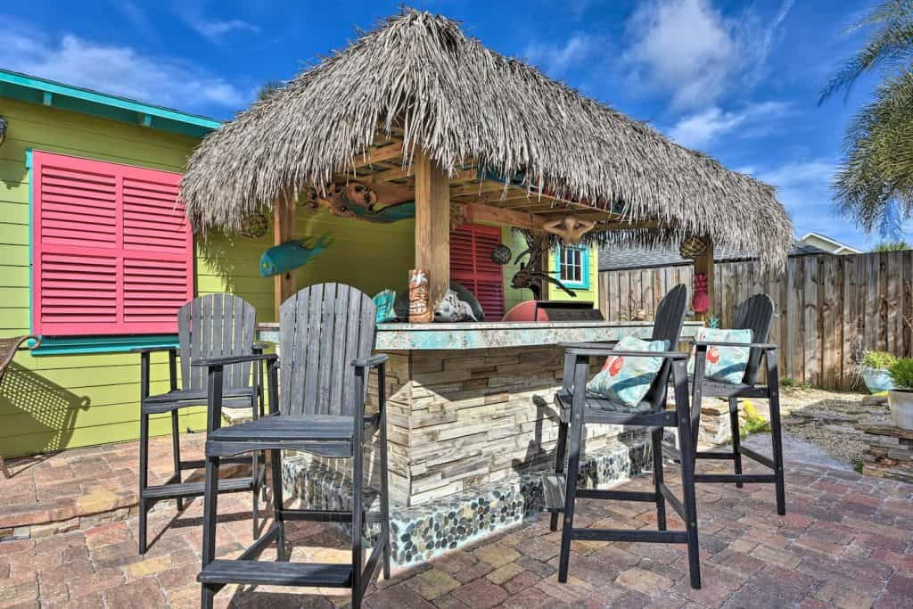 Photo of a brightly colored studio with a tiki hut bar at an Airbnb in Florida.