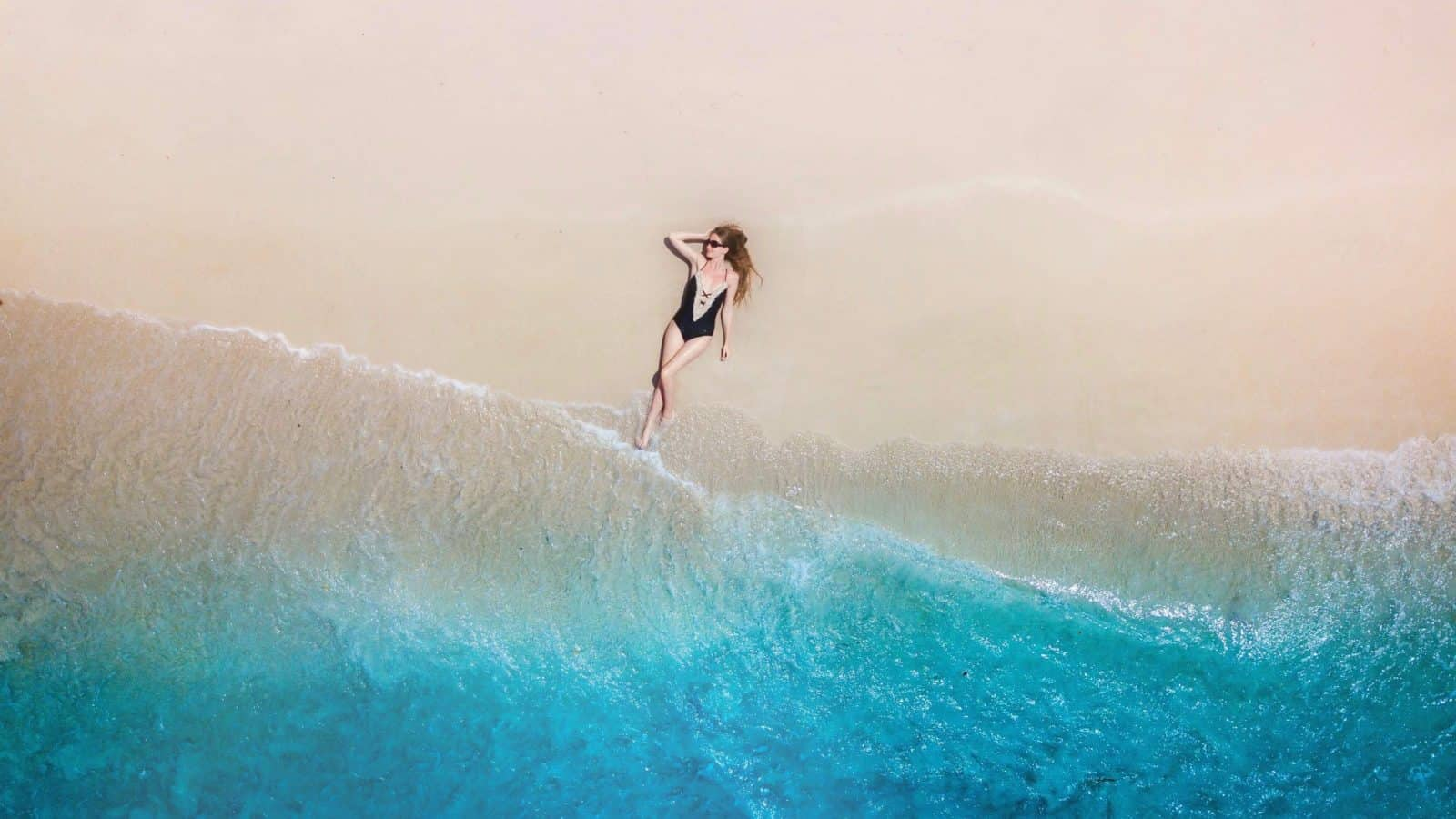 An aerial shot of a girl on a beach in an article about quotes about the beach