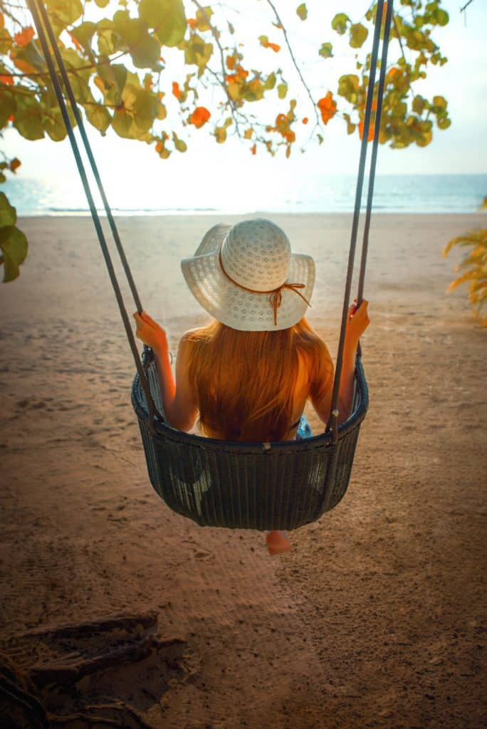 A girl on a swing on the beach in an article about beach quotes for Instagram