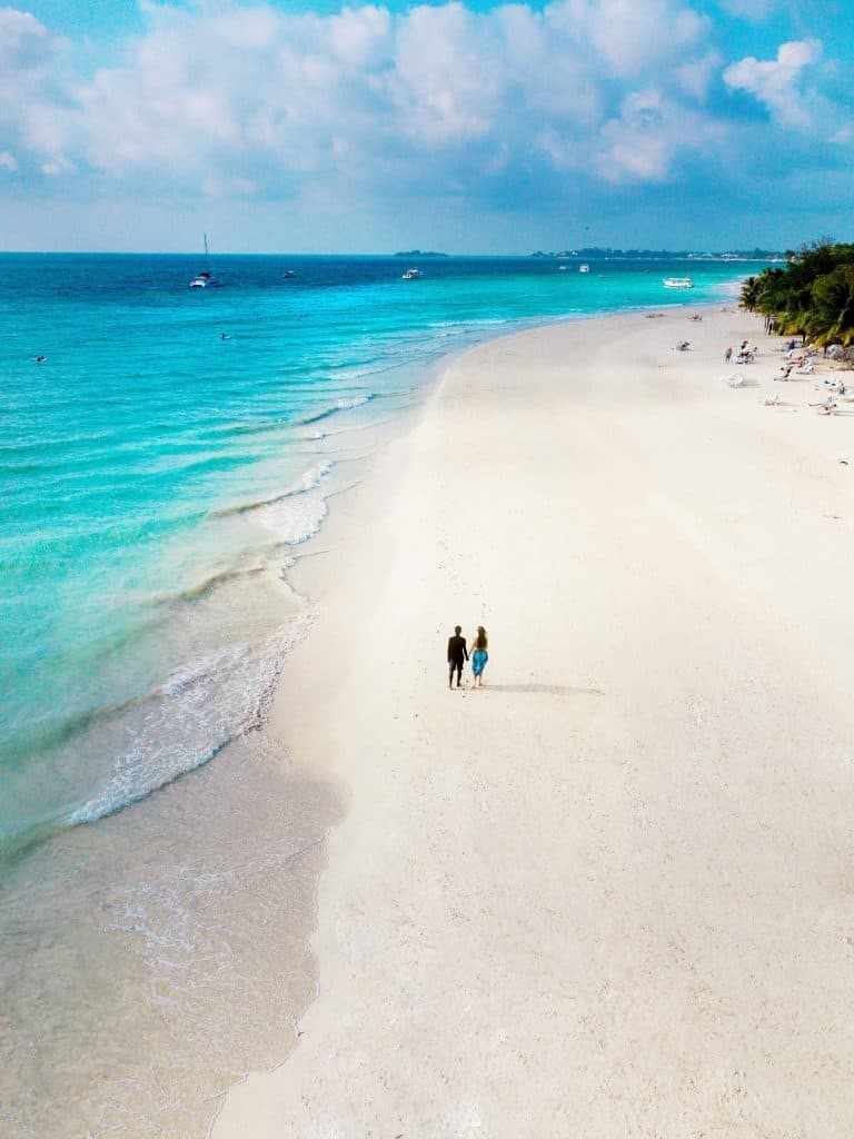 An aerial view of a couple on the beach in an article about beach saying for everyday