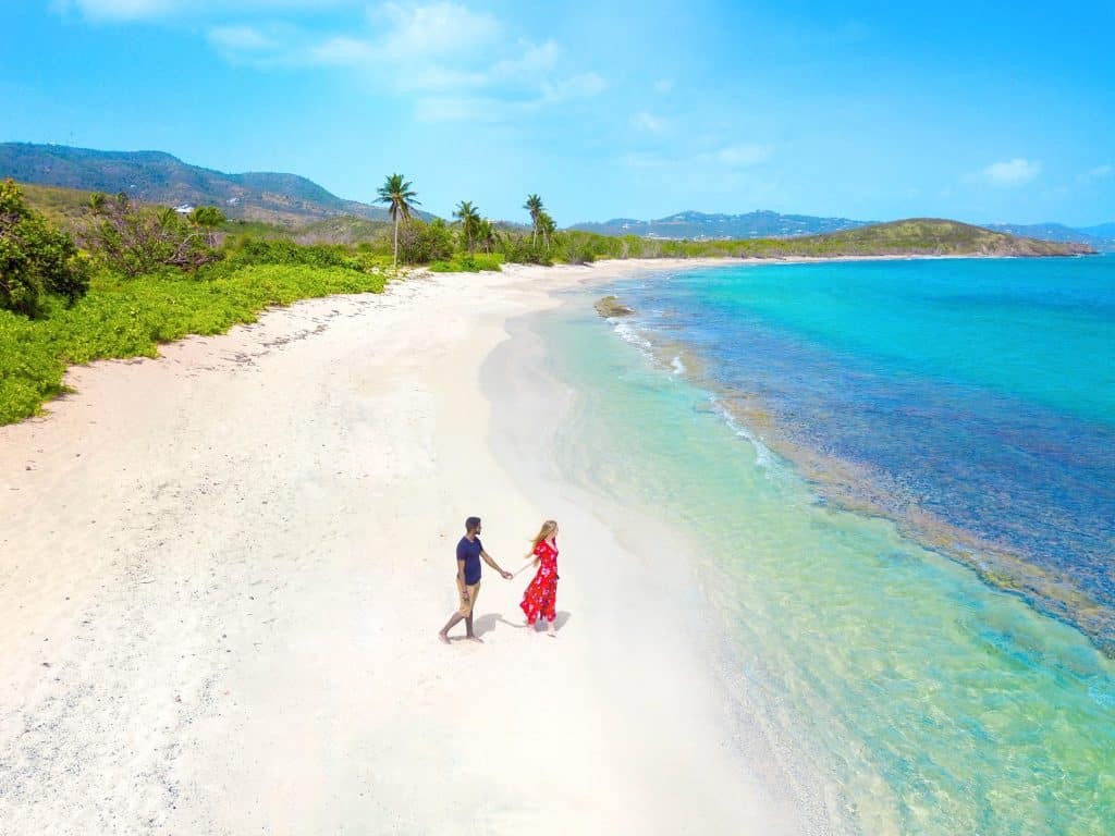 a couple walking on the beach in an article with romantic beach quotes