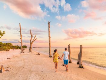 A couple holding hands on Lovers key beach